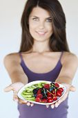 Beautiful young woman holding out plate of fruit against white background