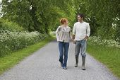 Full length of a smiling couple holding hands and walking on country road