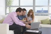 Male real estate agent using laptop with couple in new home