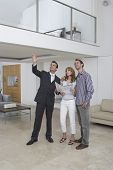 Full length of a male real estate agent showing couple new home