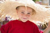 Young boy in red shirt, with large sun hat