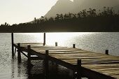 stock photo of dock a lake  - Silhouetted image of wooden dock in lake at sunset - JPG