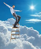 young confident businessman standing at the ladder high in the sky balancing on top