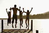 stock photo of preteen  - Rear view of father with children holding hands while jumping off a jetty - JPG