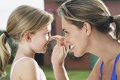Closeup-Seitenansicht einer Mutter, die Anwendung von Sonnencreme an zufriedene Tochter Nase im freien