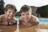 Portrait of two smiling shirtless boys leaning on pool's edge