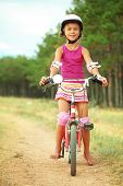 Young kid girl riding her bike outdoors