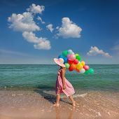 Young woman walking on the beach with colored balloons / Summer relaxation