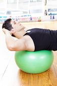 Handsome man exercising with Pilates ball