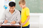 cheerful young male teacher grading school boy's work