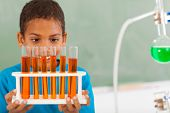 cute male primary school student in science class holding tubes