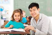 stock photo of schoolgirls  - caring elementary school teacher helping student in classroom - JPG