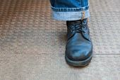 stock photo of stippling  - Horizontal color landscape of trendy laced up leather boots and stylish turned up denim jeans on a stippled tiled ground - JPG