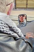 Reflections of Caucasian motorbiker in rear view mirror