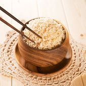 Close up cooked organic basmati brown rice in wooden bowl with chopsticks on dining table.