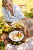 Smiling retired couple eating and drinking outdoors