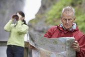 Hombre leyendo el mapa con borrosa mujer mirando a través de binoculares en el fondo