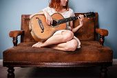 Beautiful Young Woman On Sofa Is Playing Guitar