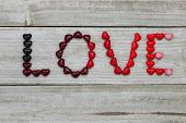 Candy hearts spell LOVE against wood background