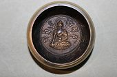 Tibetian singing bowl carved inside with Buddha holding singing bowl in hand