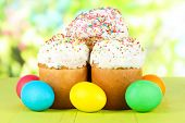 Sweet Easter cakes with colorful eggs on table on bright background