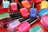 Group of bright nail polishes, on red background