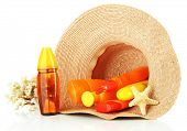 Bottles with suntan cream in hat isolated on white