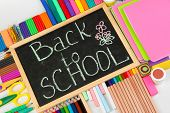 The words 'Back to School' written in chalk on the small school desk with various school supplies cl