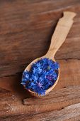 Cornflowers in wooden spoon on table close-up