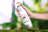 Hand holding mosquito spray on nature background