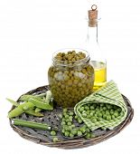 Fresh  and canned peas in glass jar on wicker mat, isolated on white