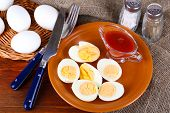 Boiled eggs on plate on wooden board on tablecloth on wooden table