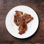Grilled T-bone Steak  On White Plate On Dark Wooden Background