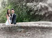 Romantic happy smart young couple on an old stone bridge leaning on the parapet smiling at the camer