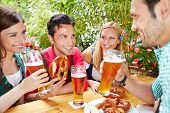 Group of happy friends talking in beer garden in summer in Bavaria