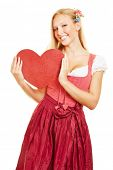 Smiling young woman in dirndl dress holding a big red heart