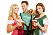 Two women and man with beer and pretzel at Oktoberfest in Bavaria