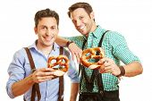 Two happy men in bavaria holding a pretzel in their hands