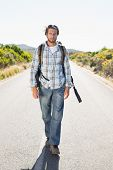 Attractive man walking on rural road on a sunny day