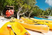 summer, canoes, activities and vacations concept - canoes on sandy beach