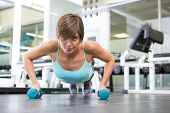 Fit brunette in plank position with dumbbells at the gym