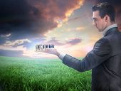 Composite image of businessman holding business team against green field under orange sky