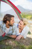 Attractive couple smiling at each other from inside their tent on a sunny day