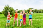 Kids playing with water guns on a meadow