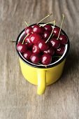 Cherries in mug on wooden background