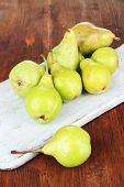 Pears on cutting board, on wooden background