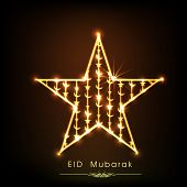 Golden star on black background for muslim community festival Eid Mubarak celebrations.