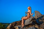 stock photo of hookah  - Girl dressed in a bikini smokes a hookah on a hillside - JPG