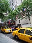 A Double-decker Tour Bus And Yellow Cabs In New York City