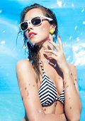 Colorful summer portrait of young attractive woman wearing sunglasses by the swimming pool